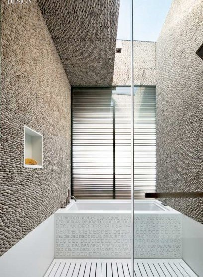 417703-One_of_the_children_s_bathrooms_has_a_skylight_walls_of_pebble_tile_and_a_Corian_shower_stall_floor_scored_with_linear_drains_.slideshow.fixedRatio.408x600